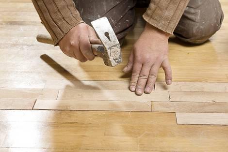 Handwerker kniet am Boden und klopft Holzstücke im Parkett fest, Foto: uwimages/fotolia.com