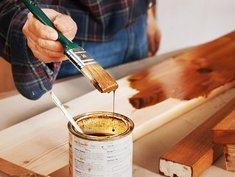 Holzfenster streichen, Mann trägt mit Pinsel Lasur auf Brett auf, Foto: Ingo Bartussek / stock.adobe.com