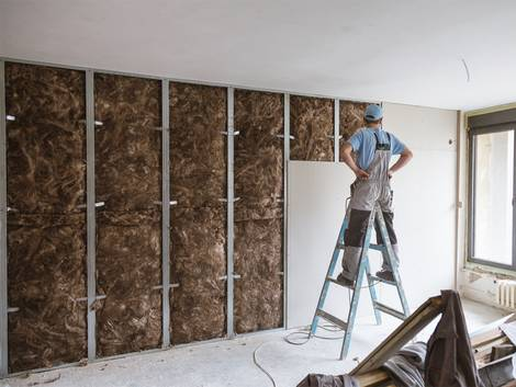Leichtbauwand, Trockenbauwand, Arbeiter steht auf einer Leiter vor einer halboffenen Leichtbauwand, gefüllt mit braunem Dämmmaterial, Foto: FluxFactory / iStock