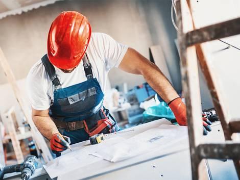 Leichtbauwand, Trockenbauwand, Bauarbeiter beugt sich über einen Bauplan, Foto: gilaxia / iStock