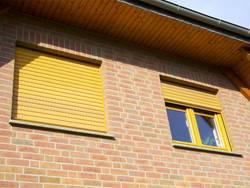 Rollladenkasten dämmen, gelber Rollladen an Backsteinhauswand, Foto: fotolia.de / Luckyboost