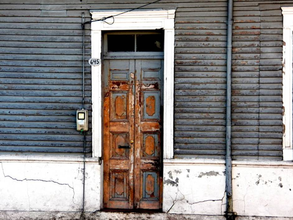 Türen streichen, Holztür, deren graue Farbe abblättert. Foto: yan Viveros / unsplash.com