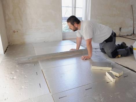 Fußbodendämmung, Handwerker verlegt Fußbodendämmplatten, Foto: IVPU e.V.
