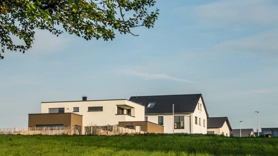 Baustile, grünes Feld, im Hintergrund Häuser mit unterschiedlichen Baustilen, Foto: focus finder / stock.adobe.com
