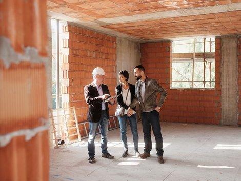Junger Paar schaut Architekt über die Schulter.