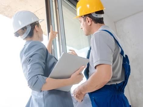 Bauabnahme, Bausachverständige mit Klemmbrett deutet auf Fenster, Handwerker sieht zu, Foto: Kzenon / stock.adobe.com