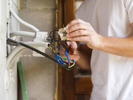 Modernisierung, Leerrohre, Mann installiert Steckdose, Foto: fotolia.de / Halfpoint