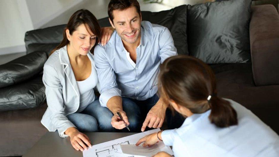 Baugenehmigung, Frau und Pärchen sitzen auf der Couch, auf dem Tisch Baupläne. Foto: goodluz / stock.adobe.com