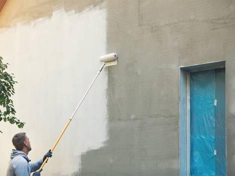 Fassade streichen, Mann streicht mit Teleskoproller eine fensterlose Fassade, Foto: iStock / ronstik