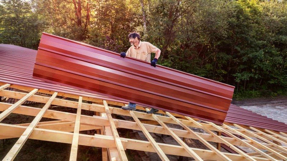 Dachplatten, Mann trägt Dachplatte auf Dach, Foto: Ingo Bartussek / stock.adobe.com