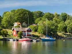 Schwedenhaus, schwedisches Holzhaus an einem See, vom Wasser ausfotografiert, Foto: Matthias Riedinger / stock.adobe.com