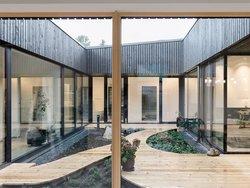 Atriumhäuser, Atrium mit Holzterrasse und Beeten. Foto: Martin Bilinovac / Steinkogler Aigner Architekten