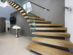 Treppenbau, DIN 18065, Treppe mit Glasgeländer und scheinbar schwebenden Stufen, die nur an einer Seite an der Wand befestigt sind. Foto: stock.adobe.com / Federico Rostagno