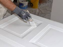 Türen streichen, weiße Tür liegt, man sieht die Hände des Malers, der die Tür mit einem Pinsel streicht. Foto: photo 5000 / stock.adobe.com