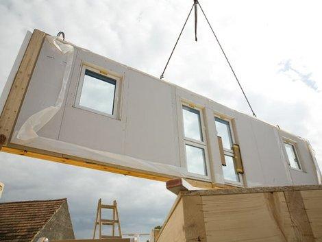 Holzständerbauweise, Fertigwand wird von Kran abgeladen, Foto: benik.at / stock.adobe.com