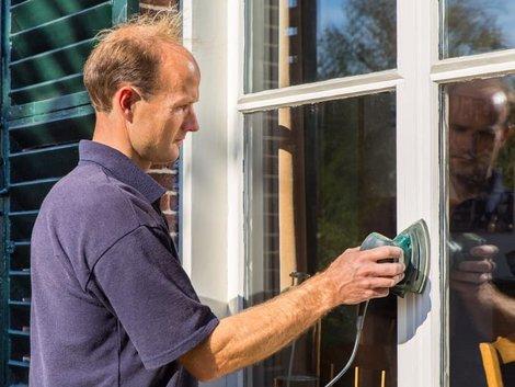 Holzfenster streichen, Mann schleift Fenster von außen ab, Foto: benschonewille / stock.adobe.com