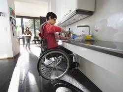 Barrierefrei bauen, Frau im Rollstuhl in einer großzügigen und offenen Küche, im Hintergrund trägt ein Mädchen ein Tablett, Foto: KfW-Bildarchiv / photothek