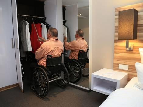 barrierefrei bauen, Mann im Rollstuhl zieht Kleiderstange mit Stab zu sich hinunter, Foto: Hotel im Schulhaus, Lorch