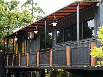 Modulhaus, Container mit überdachtem Balkon und vielen Fenstern, Foto: Aisyaqilumar / stock.adobe.com