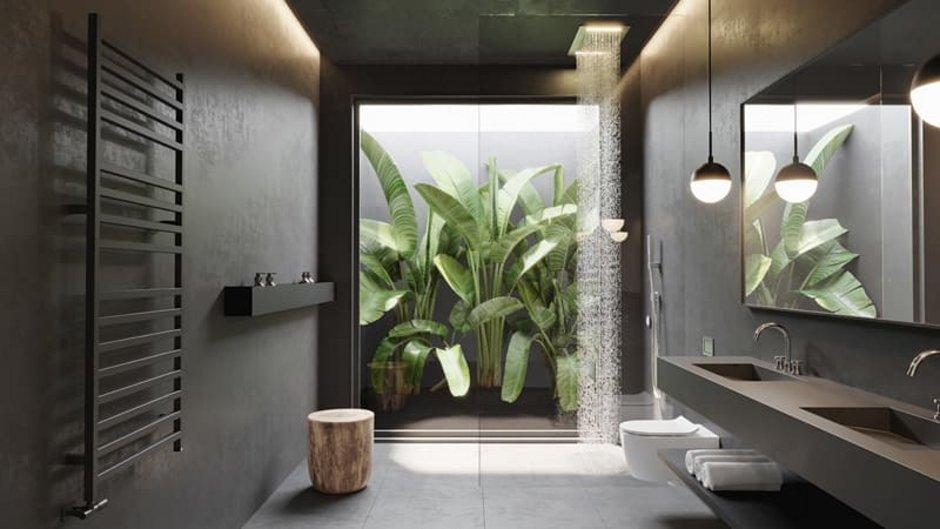 Sichtbeton, dunkelgraues Badezimmer mit großem Fenster zu einem bepflanzten Atrium. Foto: Michael / stock.adobe.com