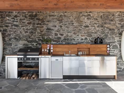 Freiluftküche, Outdoorküche, eine große Küche auf der Terrasse, Steinwand, Foto: iStock / piovesempre