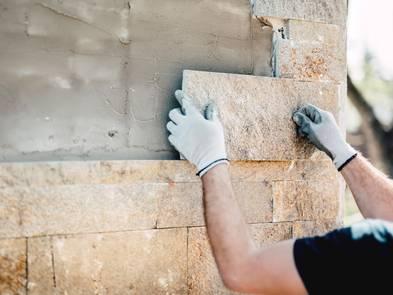 Fassadenkonstruktion, Hände eines Handwerkers, der gerade eine Steinplatte an eine Hauswand mauert, Foto: Bogdanhoda / iStock