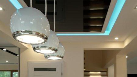 Beleuchtung, Wohnzimmerdecke mit Hängeleuchten, indirekter Beleuchtung, Farbstreifen und Spots. Foto: Ornavi / stock.adobe.com