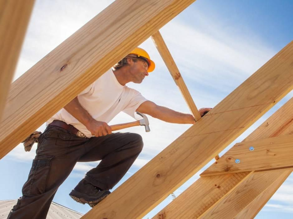 Dachstuhl, Sachstuhl selbst bauen, Blick von innen auf den Dachstuhl, ein Zimmermann klettert einen Dachbalken nach oben, mit dem Hammer in der Hand, foto: sculpies / stock.adobe.com