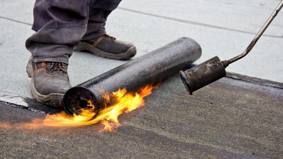 Dachpappe, Nahaufnahme der Schweißbahn, zu sehen sind die Füße des Handwerkers und die Flamme des Schweißbrenners, Foto: Deminos / stock.adobe.com