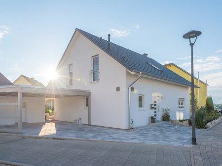 Einfamilienhaus, weißes Haus, von der Seite fotografiert, mit Carport und gepflasterter Einfahrt, Foto: schulzfoto / stock.adobe.com