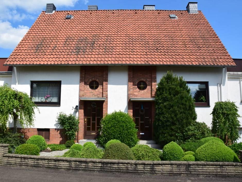 Doppelhaus, älteres Doppelhaus mit kugelförmig gestutzten Büschen im Vorgarten, Foto: stock.adobe.com / hydebrink
