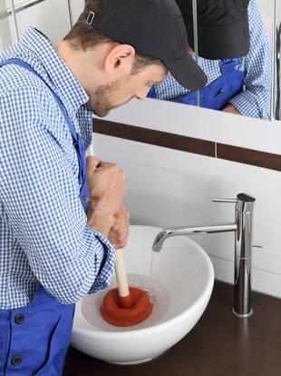 Abfluss verstopft, Mann mit Saugglocke am Waschbecken, Foto: RioPatuca Images / fotolia.de