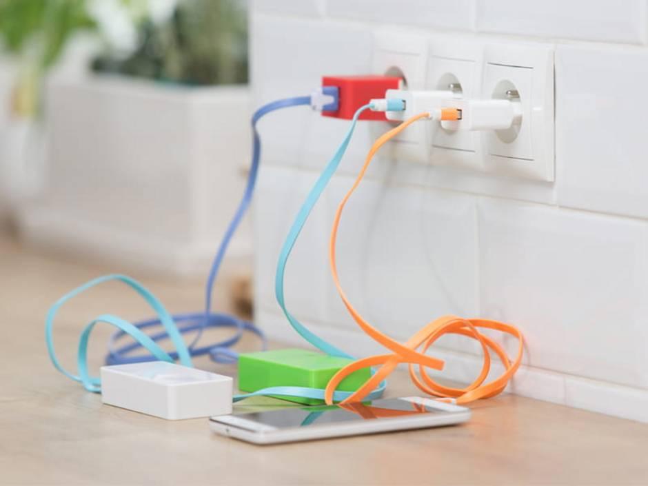 Gleichstrom, Wechselstrom, zwei Strombänke und ein Smartphone hängen an bunten Ladekabeln an der Steckdose. Foto: wip-studio / stock.adobe.com
