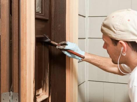 Türen streichen, Handwerker streicht Tür mit Pinsel in brauner Farbe, Foto: BanksPhotos / iStock