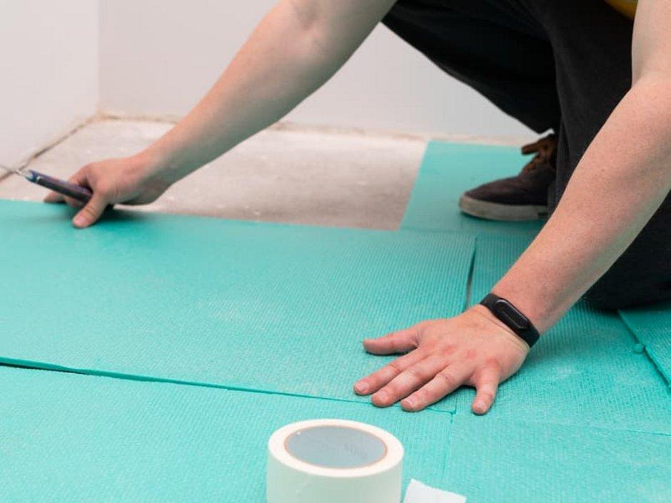Laminat selbst verlegen, Handwerker verlegt Schutzschicht auf Estricht, Foto: iStock / Ocskaymark