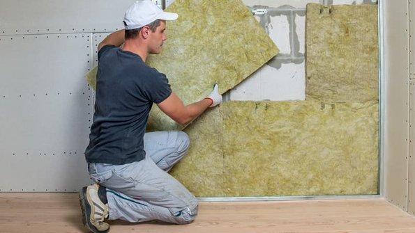 Minerwalwolle, Mann baut Mineralwolle in Trockenbauständerwerk ein, Foto: bilanol / stock.adobe.com