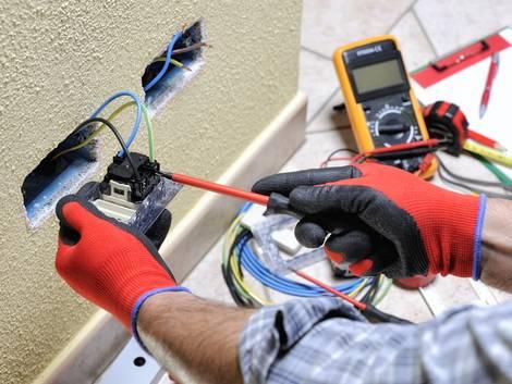 Elektroinstallation, ein Elektriker überprüft eine Steckdose, Foto: francescomou / stock.adobe.com