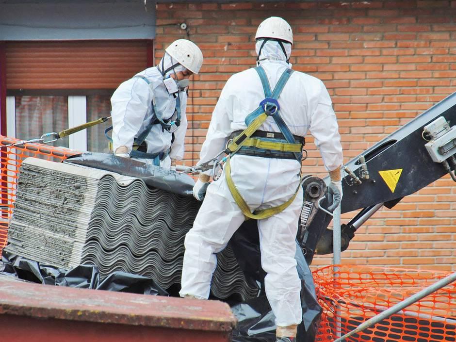 Asbestsanierung, zwei Arbeiter in weißen Schutzoveralls und mit Maske auf dem Dach eines Wohnhauses, Foto: Ecology / stock.adobe.com