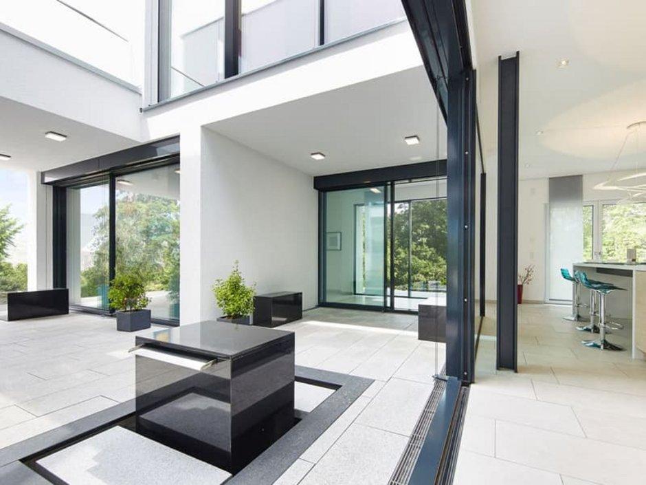 Atriumhäuser, modernes Haus aus Beton und Glas, viele gerade Linien. Foto: Okal
