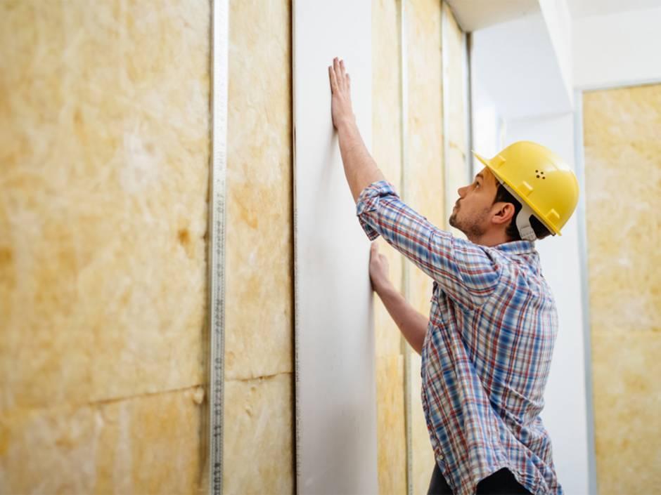 Leichtbauwand, Trockenbauwand, Mann bringt Gipsplatten an Ständerwerk an. Foto: TommL / iStock