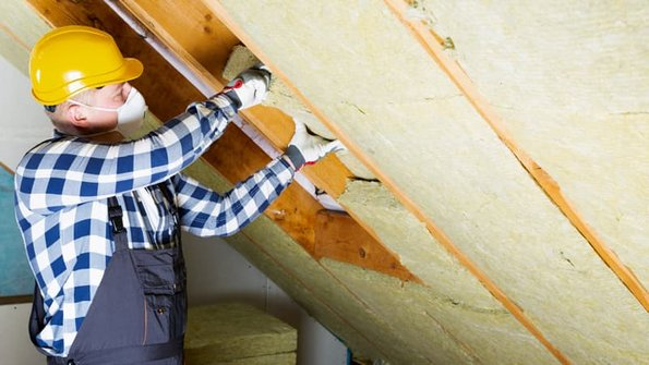 Mineralwolle, Mann bringt Mineralwolle zwischen zwei Dachsparren an. Foto: artursfoto / stock.adobe.com