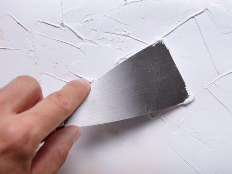 Wand verputzen, Heimwerker bearbeitet Putzoberfläche mit einer Spachtelkelle, Foto: iStock.com / AndreyPopov