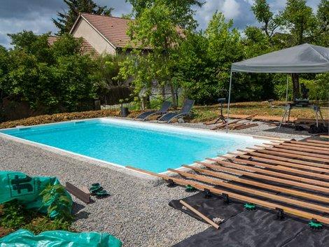 Swimmingpool, fertiges Becken, rundherum wird gerade die Querlattung für eine Terrasse montiert. Foto: Eléonore H / stock.adobe.com