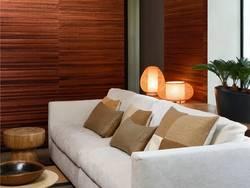 Naturtapeten, modernes Wohnzimmer mit hellem Sofa und brauner Tapete aus Bananenblättern, in horizontale Streifen geschnitten. Foto: Arte