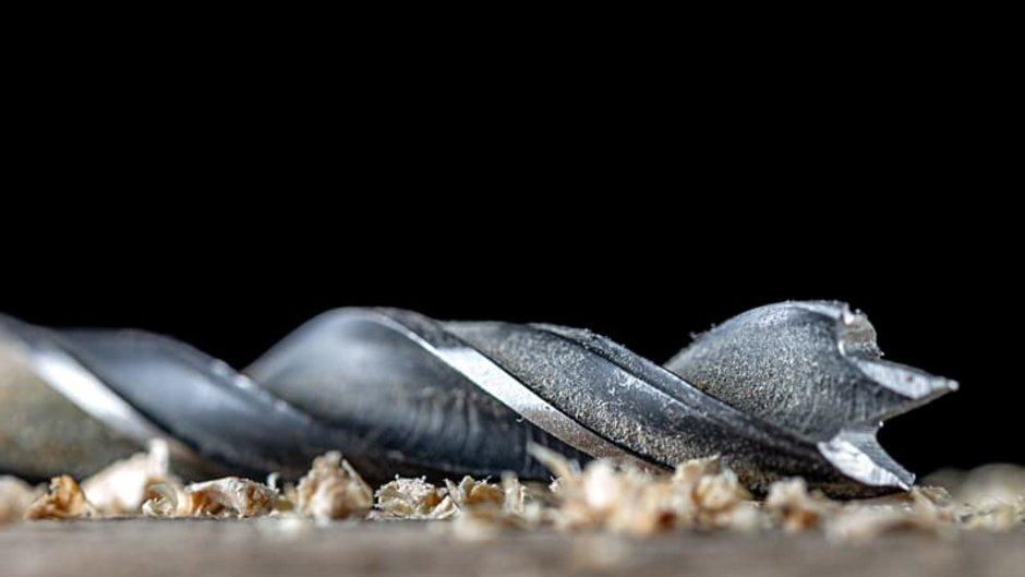 richtig bohren, Nahaufnahme eines Holzbohrers, der auf einer Oberfläche liegt, Holzspäne, Foto: ruslan_khismatov / stock.adobe.com