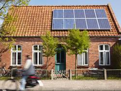 Photovoltaikanlage auf dem Dach eines Backsteinhauses, Foto: ideeone / iStock