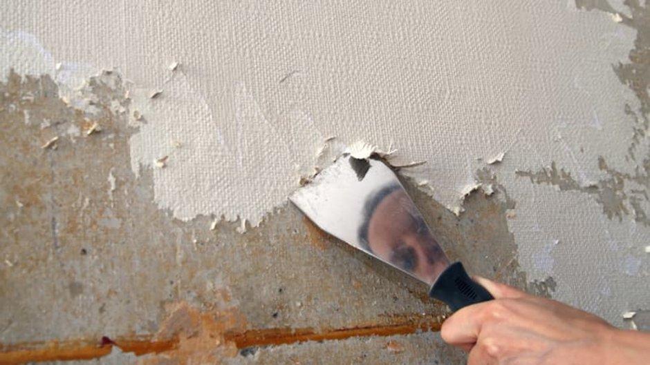 Tapeten entfernen, Mann spiegelt sich im Spachtel, mit dem er alte Tapeten ablöst, Foto: iStock.com / kelvinjay