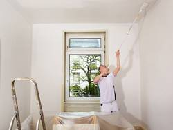 Decke streichen, Mann streicht Decke mit einem Teleskoprolle, das Zimmer ist zum Teil mit Folie abgedeckt. Foto: Ingo Bartussek / stock.adobe.com