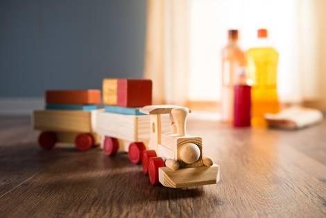 Holzeisenbahn auf Holzfußboden. Im Hintergrund Pflegeprodukte. Parkett, Schäden, Foto: stokkete/fotolia.com