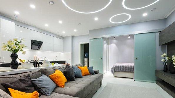 Beleuchtung, Wohnzimmer mit Spots und kreisförmiger Beleuchtung in der Decke, Blick auf das Sofa, Foto: starush / stock.adobe.de